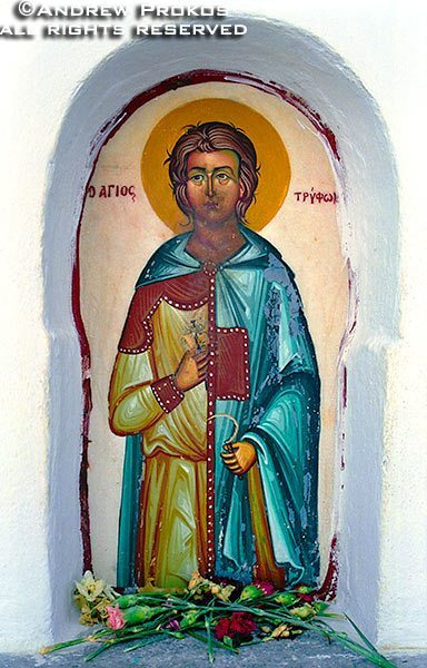 A whitewashed niche containing a colorful painted icon of a Greek Orthodox saint, Santorini, Greece