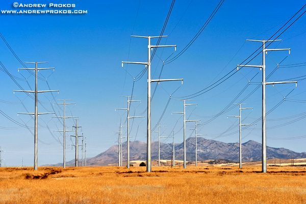 A group of steel electricity transmission towers set in a sparse Southern Idaho landscape