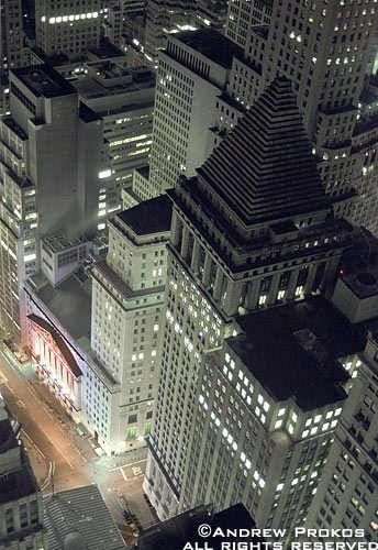 An aerial view of the skyscrapers along Wall Street and the New York Stock Exchanget at night