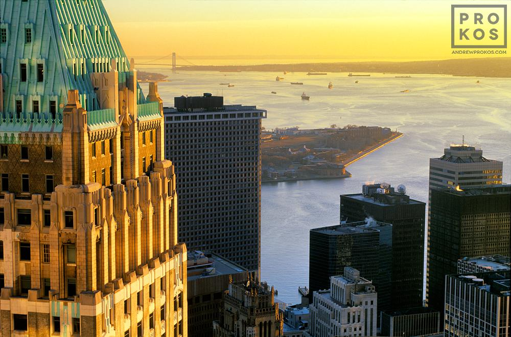 A view of 40 Wall Street (The Trump Building), the Financial District, and New York Harbor at Sunset