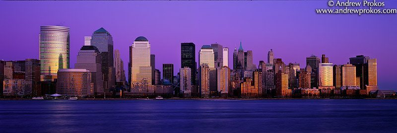 A panoramic skyline of Lower Manhattan at dusk as seen from New Jersey