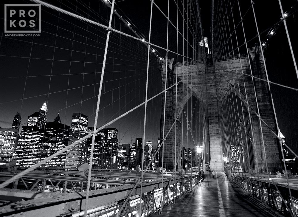 A black and white view of the suspension cables of the Brooklyn Bridge at night, New York City