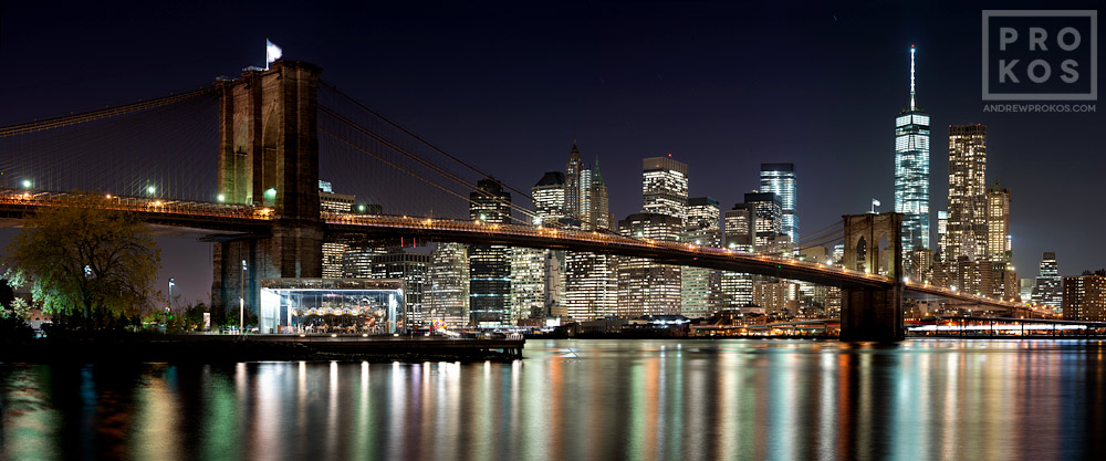 A panoramic skyline of the Brooklyn Bridge and Lower Manhattan at Night, New York City.