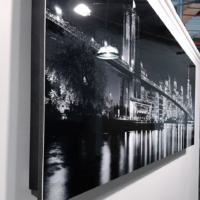 "A lateral view of the 60 inch limited edition HD metal print of ""Panoramic Skyline of Brooklyn Bridge and Lower Manhattan at Night"" showing the black metal float mount attached to rear."