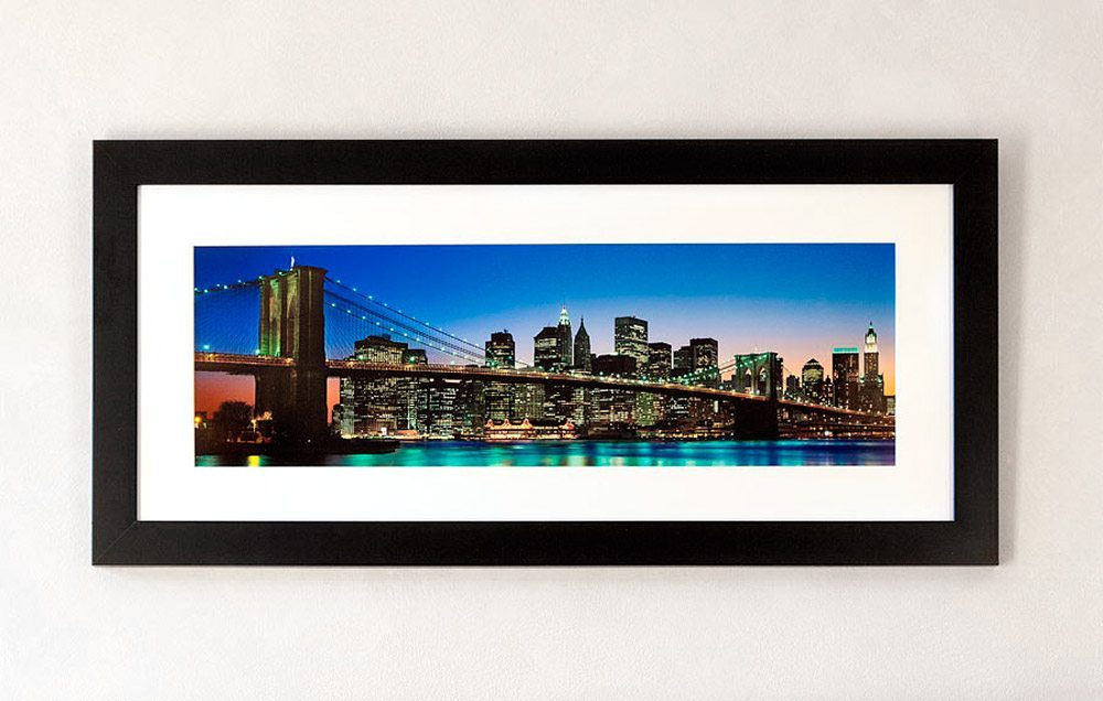 """A framed fine art print of """"Panoramic Skyline of Brooklyn Bridge and Lower Manhattan at Twilight"""" by photographer Andrew Prokos."""