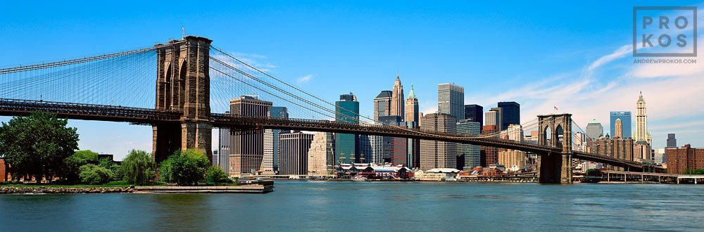 A panoramic skyline of the Brooklyn Bridge and Lower Manhattan during the daytime, New York City.