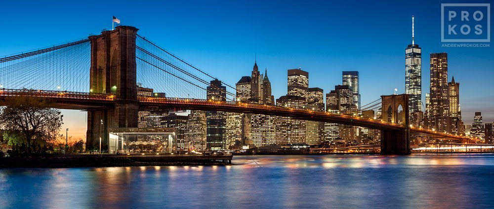 A panoramic skyline of the Brooklyn Bridge and Lower Manhattan at twilight, New York City.