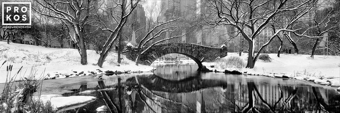 A black and white panoramic view of Gapstow Bridge and the Lake in Central Park in Winter