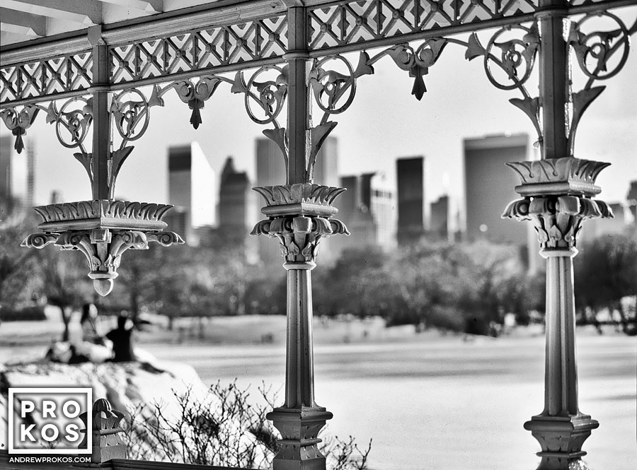 A black and white view of the frozen lake and Midtown skyline from the cast-iron gazebo in Central Park in Winter