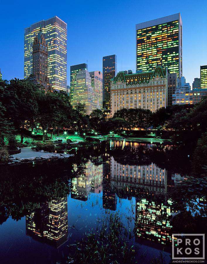 A view of the skyscrapers along Fifth Avenue, the Plaza Hotel, and the Pond in Central Park at dusk