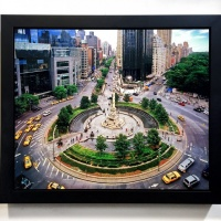 """A 20x24 high-definition metal print of """"VIew of Columbus CIrcle I"""" by photographer Andrew Prokos, framed in a solid matte black wood frame."""