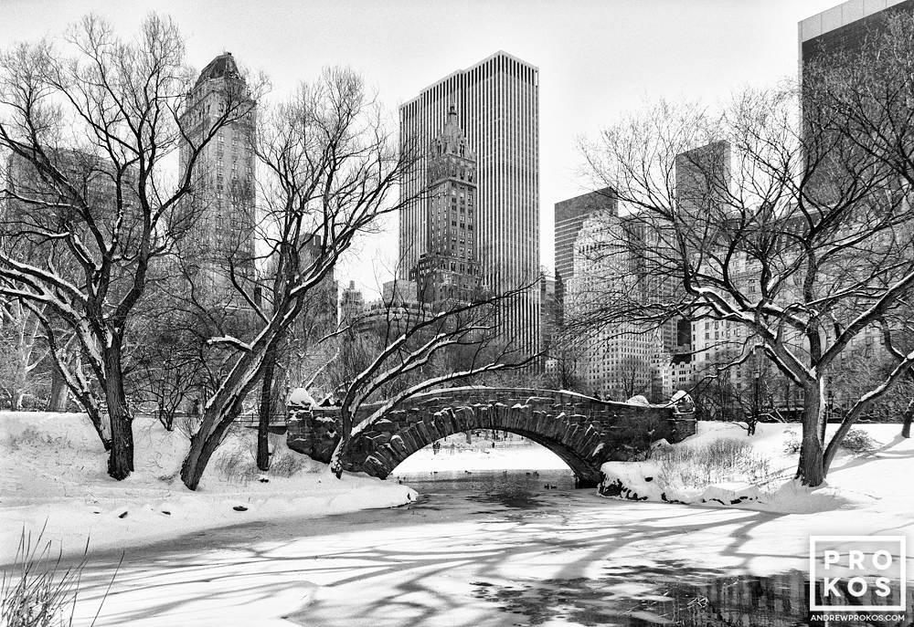 A black and white view of Central Park's Gapstow Bridge and the Pond in Winter, New York City