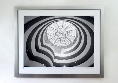 A 30x40 inch black and white photo of the Guggenheim Museum interior framed with a brushed silver wood frame