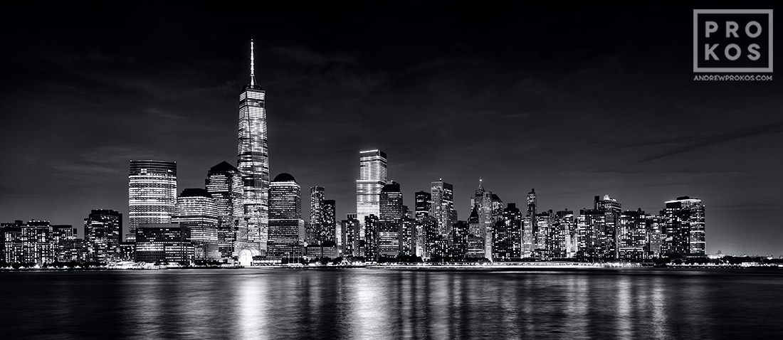 A panoramic skyline of Lower Manhattan, Hudson River, and the World trade Center at night in black and white as seen from New Jersey