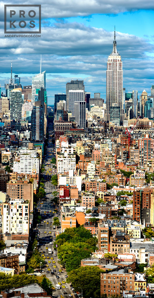 A vertical panoramic cityscape of Manhattan and the Empire State Building as seen from SoHo during the day.