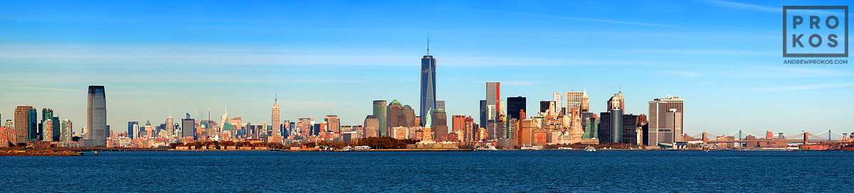 A panoramic skyline of New York City, World Trade Center, Statue of Liberty, and New York Harbor during the day.