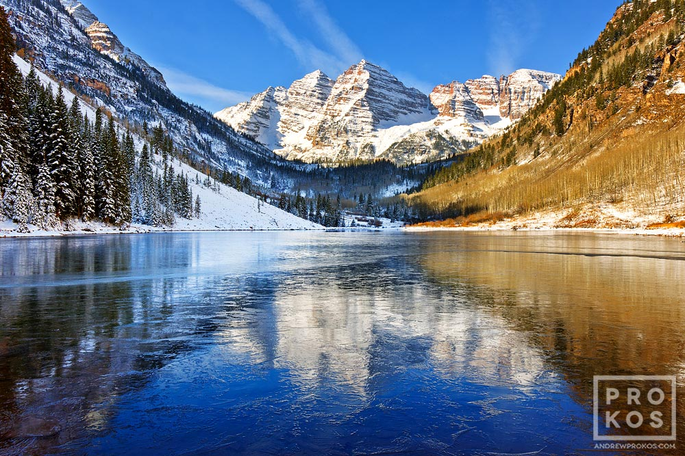 A landscape photo of the Maroon Bells mountains reflected on the frozen surface of Maroon Lake, near Aspen, Colorado.