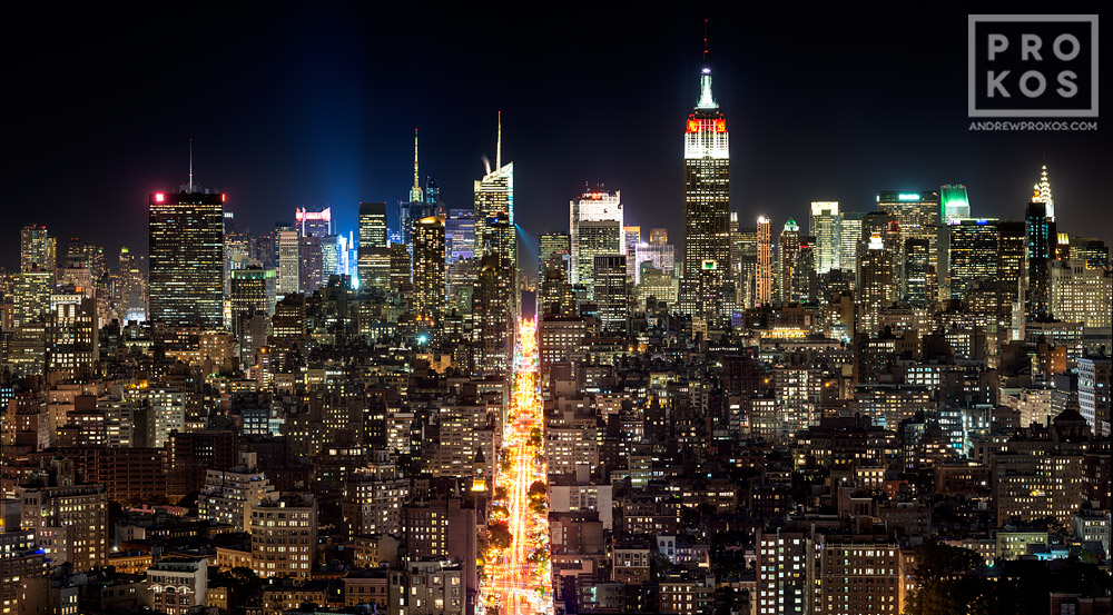 A panoramic cityscape of the buildings of Midtown Manhattan, and the Empire State Building at night.