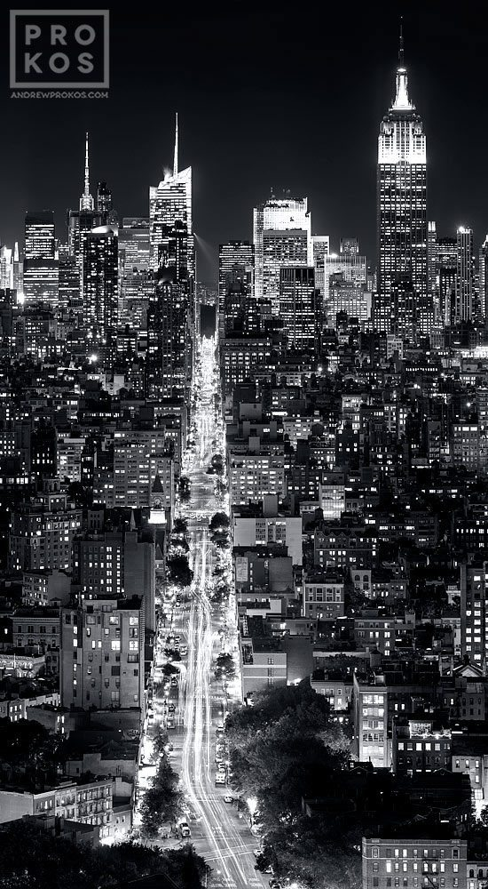 A vertical panoramic cityscape of Manhattan at night in black and white.