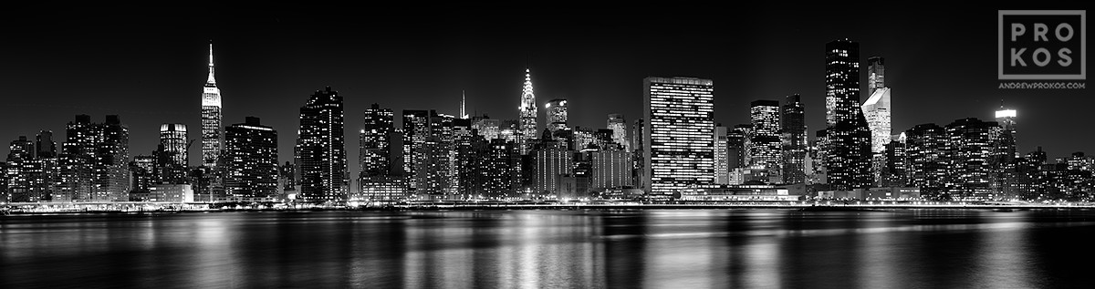 An ultra-wide long-exposure skyline of Midtown Manhattan at night in black and white, New York City.
