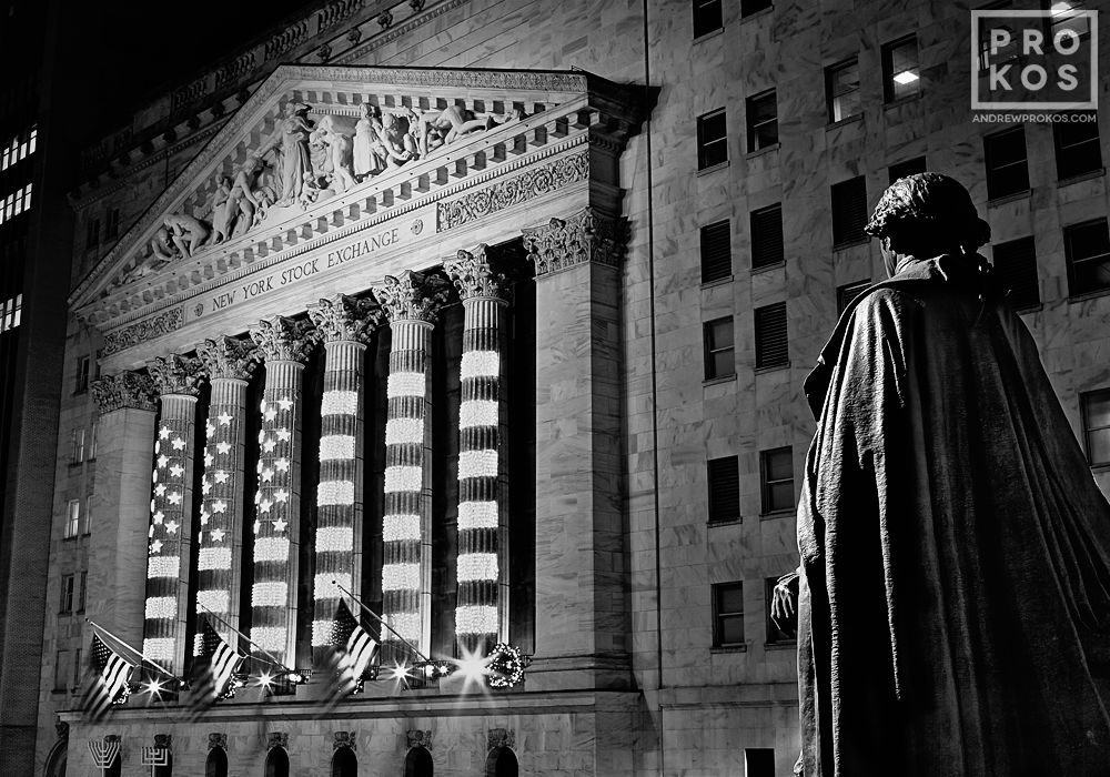 A view of the New York Stock Exchange and statue of George Washington at night in black and white