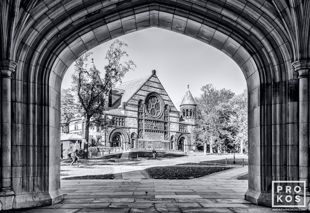 A black and white view of Alexander Hall framed in the arch of Blair Hall on the campus of Princeton University, New Jersey