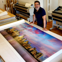 "Photographer Andrew Prokos with an 80 inch limited edition print of ""Panoramic View of Lower Manhattan and the World Trade Center at Dusk"""