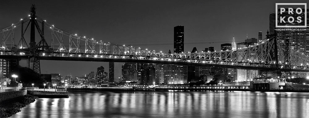 A panoramic view of the Queensboro Bridge and NYC skyline at night in black and white, New York City