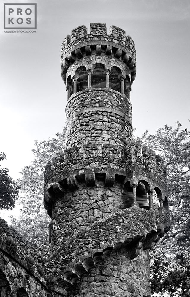 A black and white photo of the tower of the Poco Iniciatico, a hidden well with arched spiral stairway in the Quinta da Regaleira gardens of Sintra, Portugal