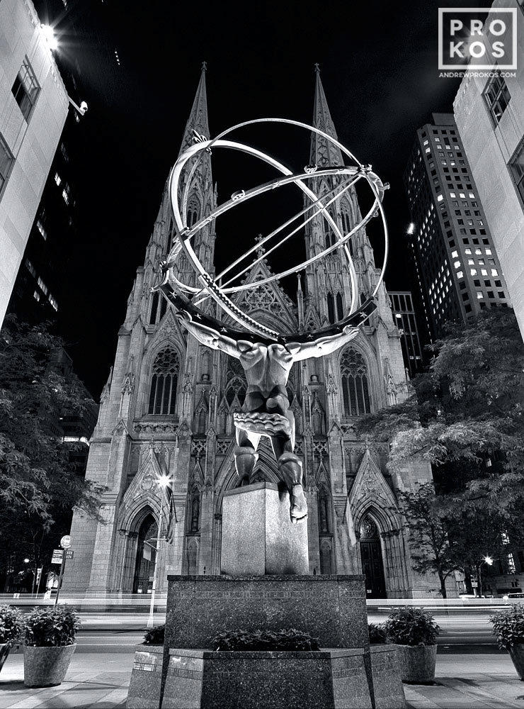 A black and white fine art photo of the Atlas statue at Rockefeller Center and St. Patrick's Cathedral at night, New York City.