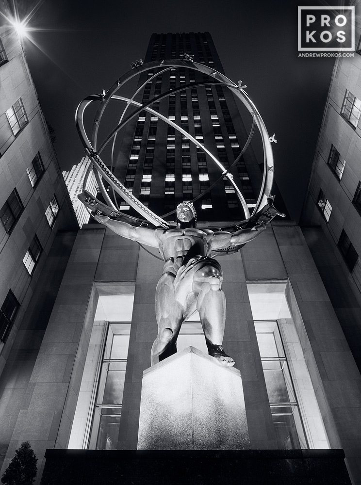 A black and white photo of the famous art deco statue of Atlas at Rockefeller Center at night, New York City