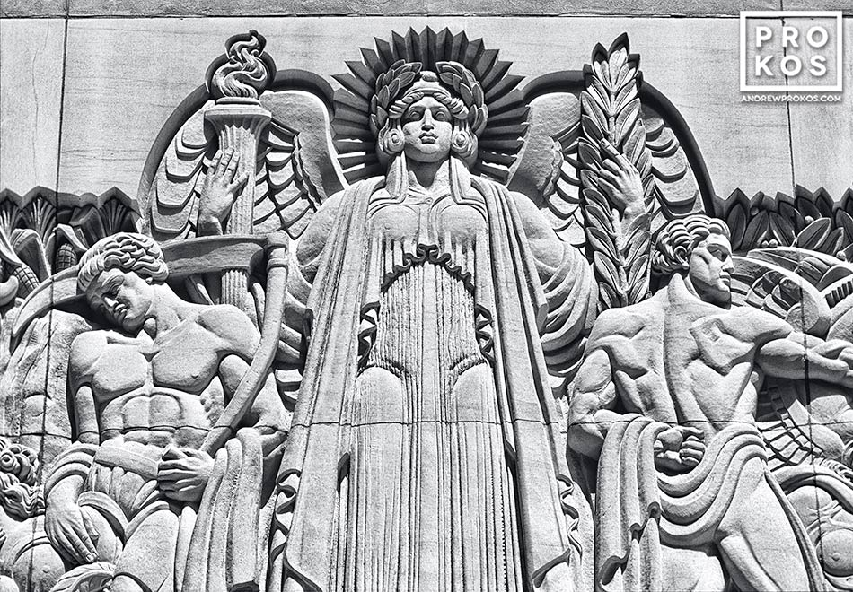 A carved stone relief in the Art Deco style at Rockefeller Center, New York City in black and white