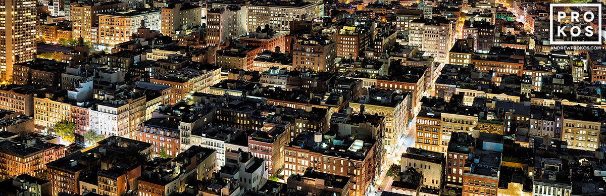 A long-exposure panoramic view of the rooftops of SoHo New York City from above at night.