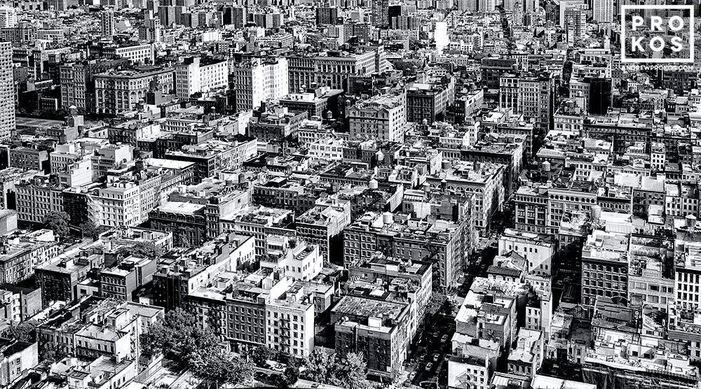 A black and white panoramic cityscape of the rooftops of SoHo, New York City as seen from above