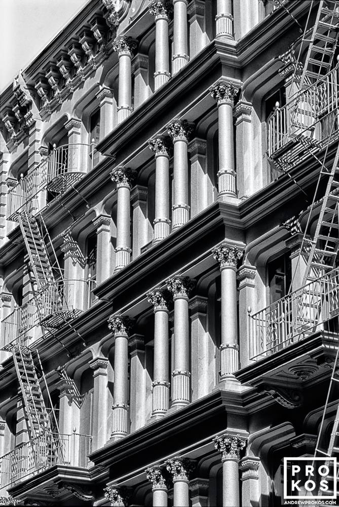 The ornate cast iron facade of a Soho loft building shown in black and white, New York City