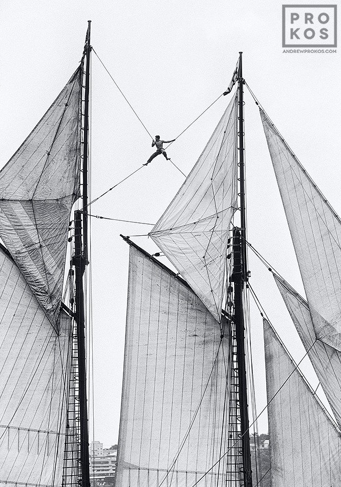 A sailor perched in the rigging of a two-masted schooner on the Hudson River
