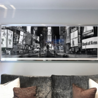 "The 90 inch print of ""Panoramic View of Times Square at Night"" framed in a high polish chrome frame."