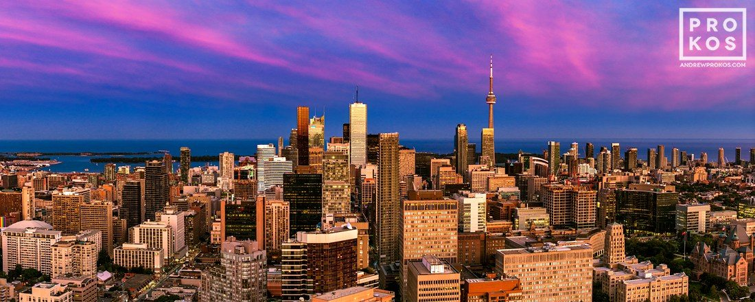 A panoramic cityscape of Toronto, Canada at dusk.