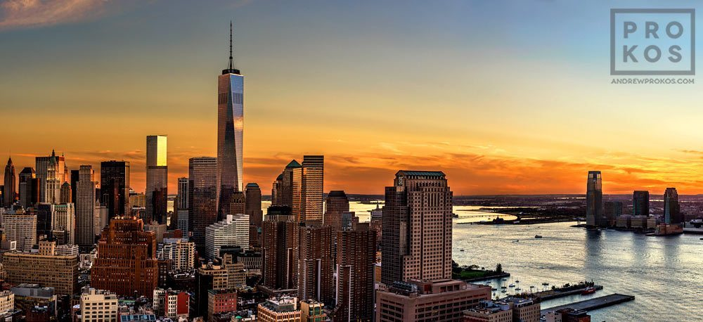 A panoramic view of the World Trade Center, Lower Manhattan, the Hudson River, and New Jersey at sunset.