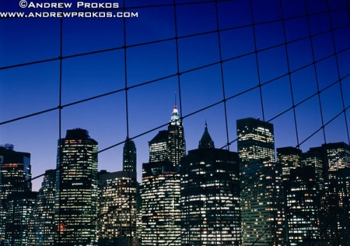 A view of Lower Manhattan as seen through the suspension cables of the Brooklyn bridge at night, New York City