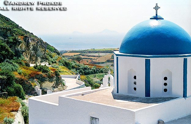 A landscape photo with a blue-domed church on the island of Santorini, Greece