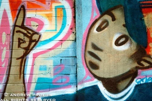 A detail from a Latin street mural in Harlem with gesturing boy, New York City