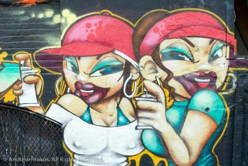A street mural of girl graffiti artists with spray paint cans, Queens.