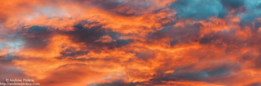 A panoramic skyscape of coral-colored clouds against a blue sky at sunset.
