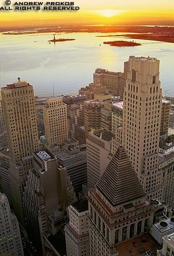 An aerial photo of Lower Manhattan, the Financial District, and New York Harbor at sunset