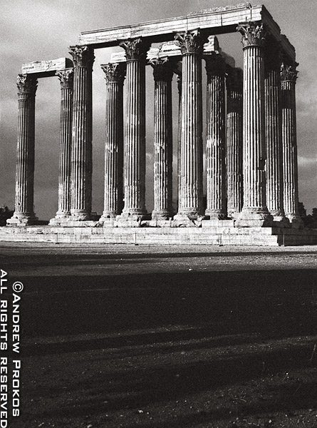 A black and white view of the ancient Temple of the Olympian Zeus in the center of modern-day Athens, Greece
