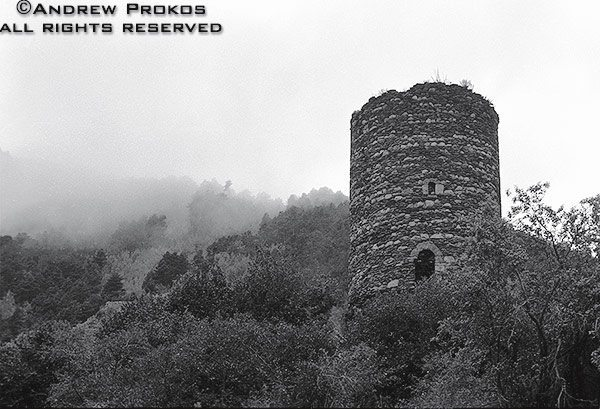 The ruins of an ancient stone tower shrouded in mist in the Pyrenees Mountains