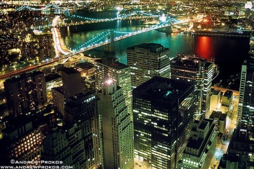 An aerial photo of Lower Manhattan, the Brooklyn Bridge, and East River at night, New York City