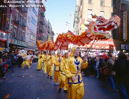 A street scene photo of men in costumes parading a dragon through Chinatown during the Chinese New Year parade, New York City