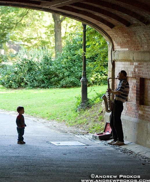 A street scene photo of a child watching intently as a saxophonist plays his horn in Central Park, NYC